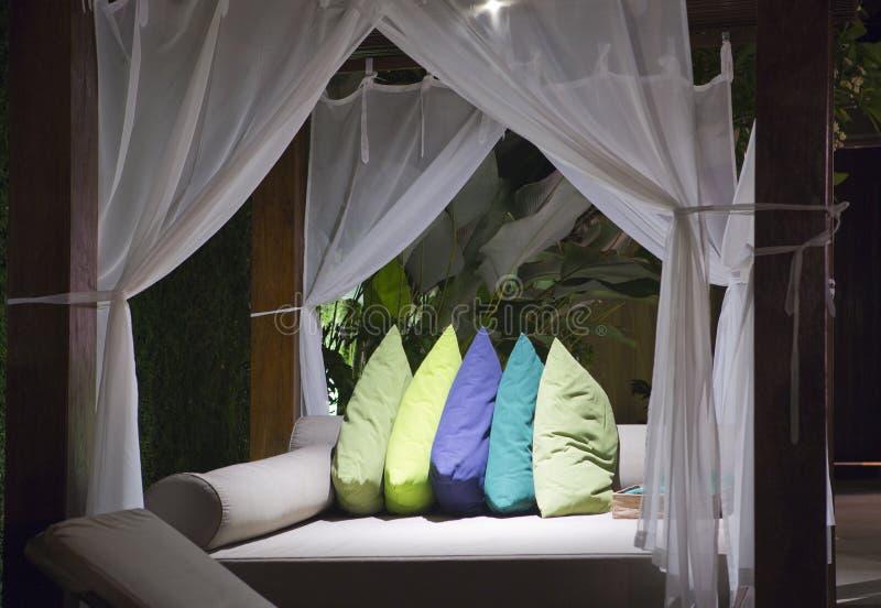 在床帷幕下的大室外床有明亮的颜色的把枕在 免版税库存照片