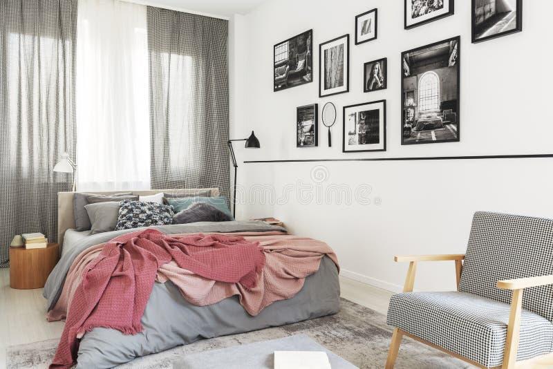 在床旁边的扶手椅子与桃红色毯子在现代明亮的卧室内部与画廊 实际照片 免版税库存图片
