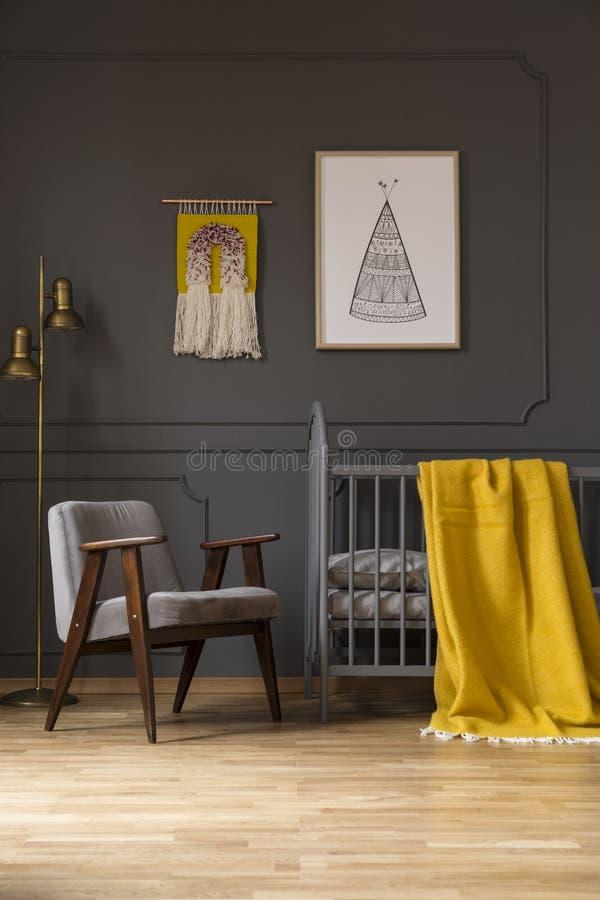 在床旁边的灰色扶手椅子与黄色毯子在婴孩` s卧室 免版税库存图片