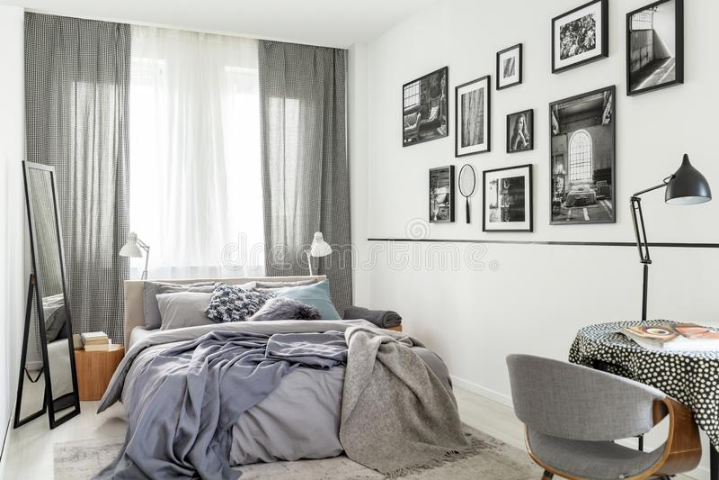 在床旁边的镜子在与照片窗口和画廊的明亮的灰色卧室内部  实际照片 免版税库存图片