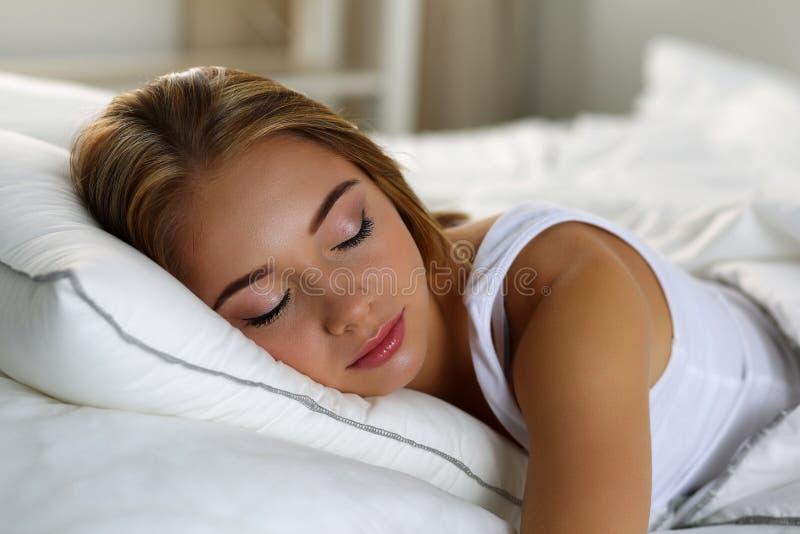 在床睡觉的年轻美丽的白肤金发的妇女画象 免版税库存图片