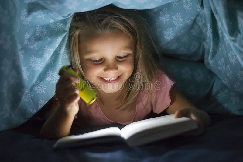 在床罩阅读书下的美好的美好和相当小的白肤金发的女孩6到8岁在黑暗在与火炬光的晚上 库存图片