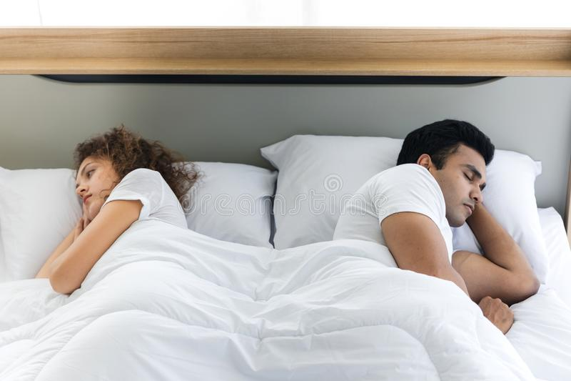 在床说谎的后面的沮丧的被注重的年轻夫妇互相 关系和问题夫妇概念 免版税库存照片