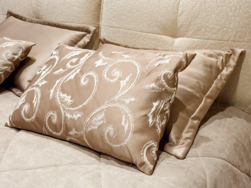 在床豪华现代样式卧室的不同的枕头红色和桃红色口气的,旅馆卧室的内部 库存照片