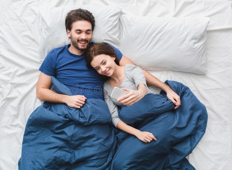 在床顶视图早晨拍selfie照片的概念女孩的年轻夫妇 免版税库存照片
