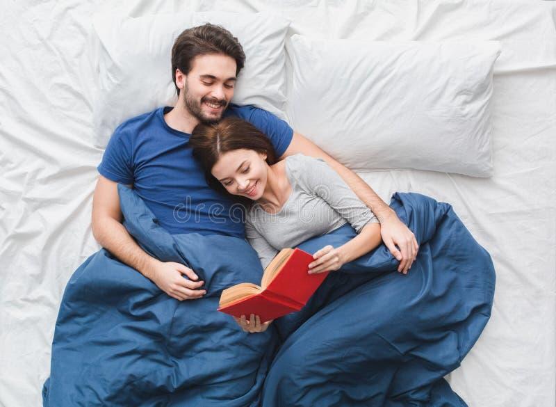 在床顶视图早晨概念读书故事的年轻夫妇 图库摄影