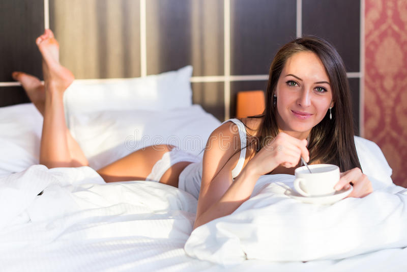 在床,饮用的咖啡上的美丽的妇女画象,拿着白色杯子 免版税库存图片