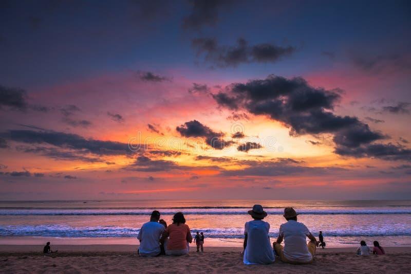 在库塔海滩,巴厘岛的旅游观察日落 免版税库存照片