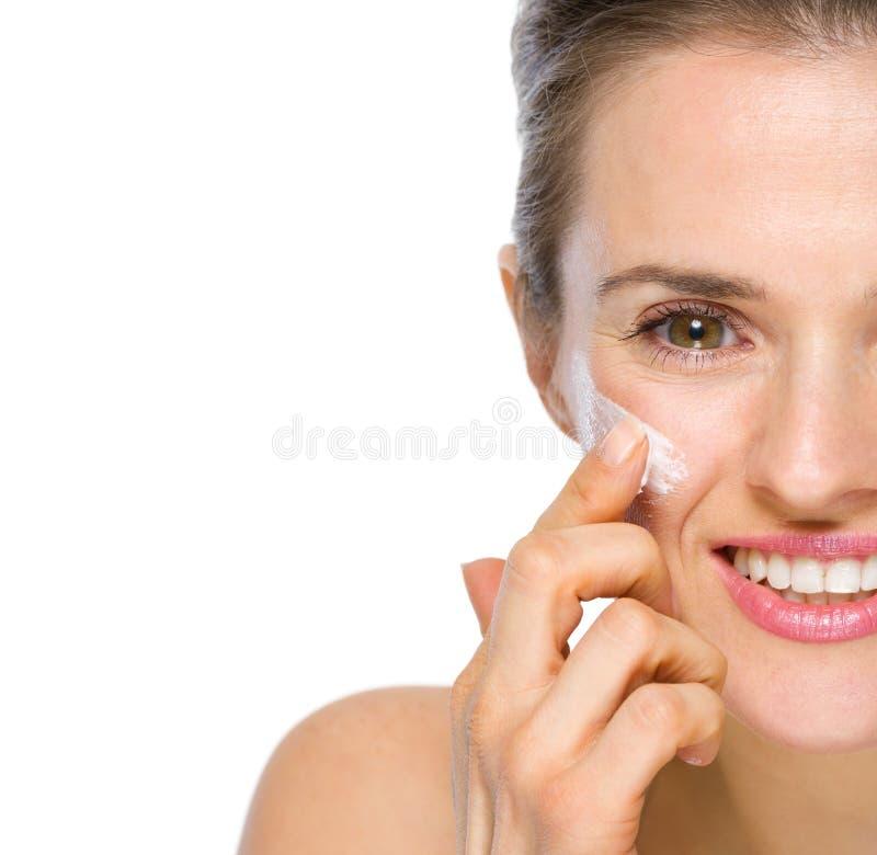 在应用在面颊的愉快的妇女的特写镜头奶油 库存照片