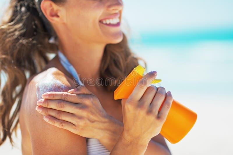 在应用太阳块奶油的微笑的少妇的特写镜头 免版税库存照片