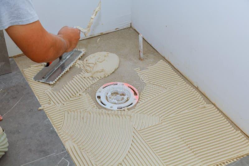 在应用瓦片前的传播的湿灰浆在卫生间地板上 免版税库存照片