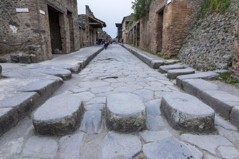 在庞贝城,意大利古色古香的罗马的被铺的街道  免版税库存图片