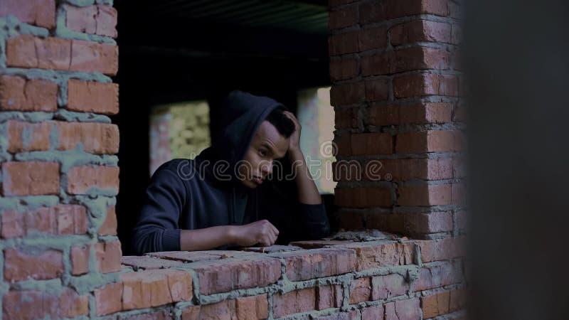 在废墟中的沮丧的少年,社会抛弃的可怜的无家可归的人 免版税库存图片