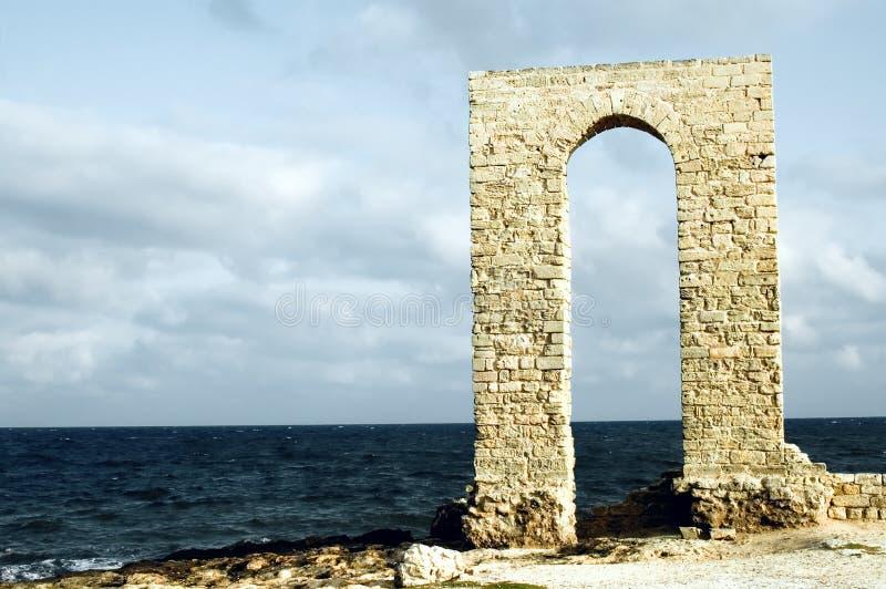 在废墟海滨视图的古老曲拱前面 库存图片