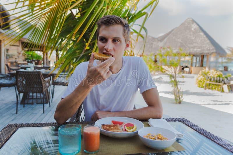 在度假在一个热带海岛吃一顿健康早餐的年轻人 库存图片