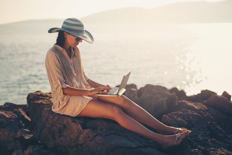在度假在网上享用与在海滩的一台膝上型计算机的旅游妇女 免版税库存图片