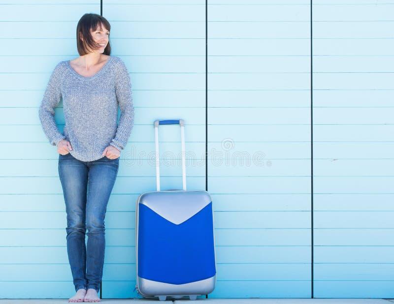 在度假微笑带着手提箱的愉快的妇女 免版税库存照片