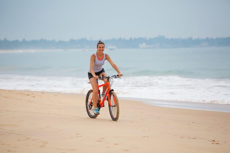 在度假骑自行车在海滩的妇女 免版税库存照片