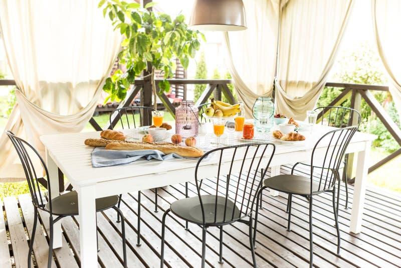 在庭院大阳台的夏天室外轻快早餐 免版税库存图片
