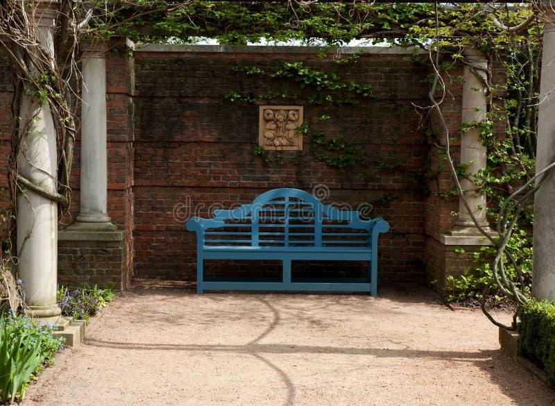 在庭院树荫处的蓝色长凳 免版税库存图片