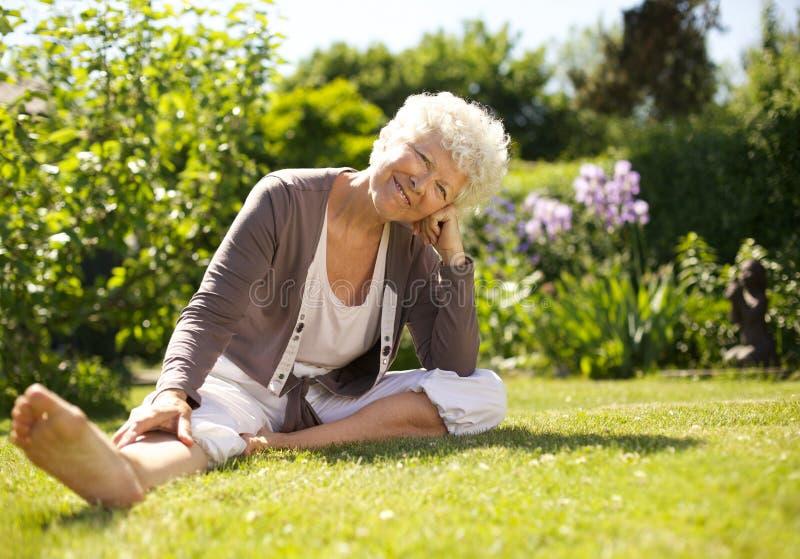 在庭院里放松的愉快资深妇女坐 免版税库存图片
