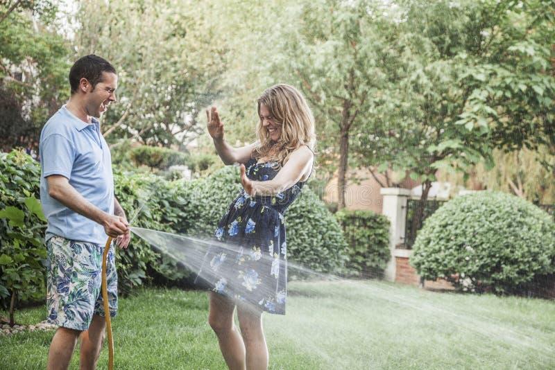 在庭院里结合使用与水管和喷洒外面 图库摄影