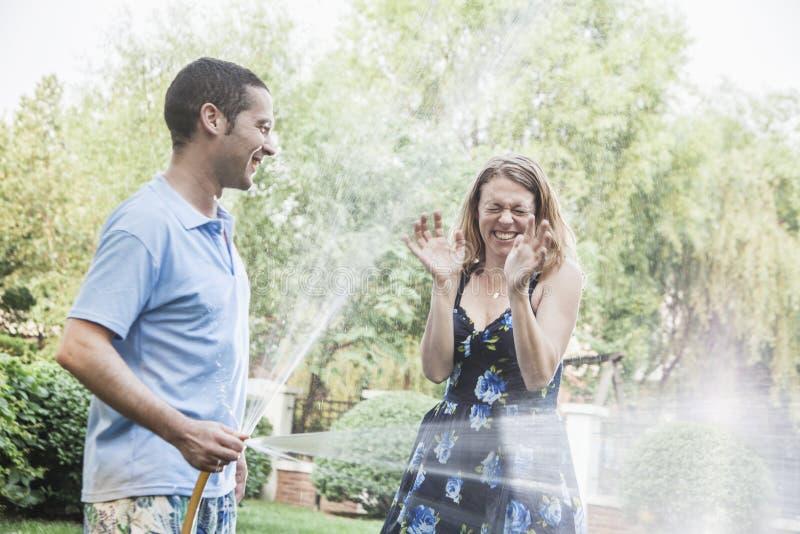 在庭院里结合使用与水管和喷洒外面 免版税库存图片