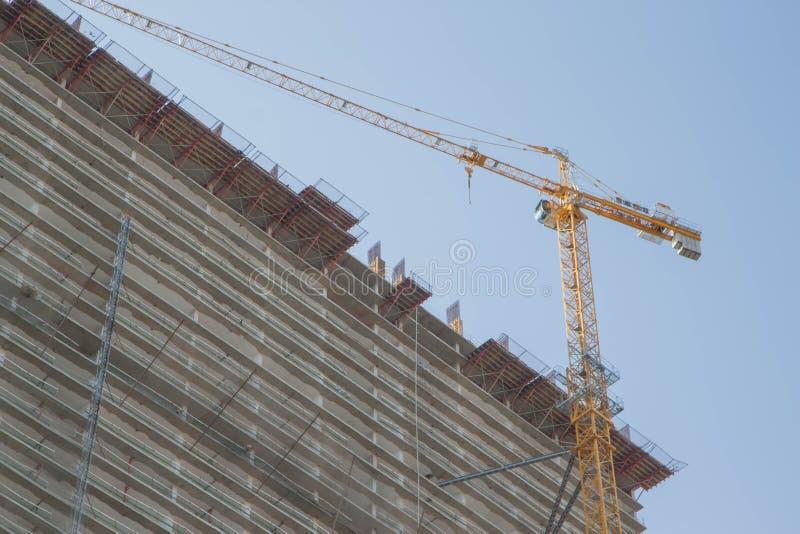 在建筑工作的一台起重机 大厦起重机 举的起重机修建多层的大厦 库存照片