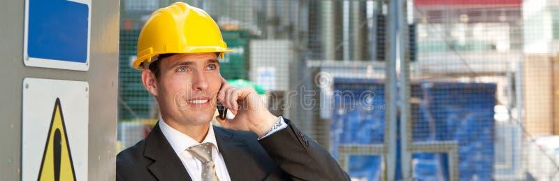 在建筑工地的建筑工人建造者谈话在电话全景 免版税库存图片