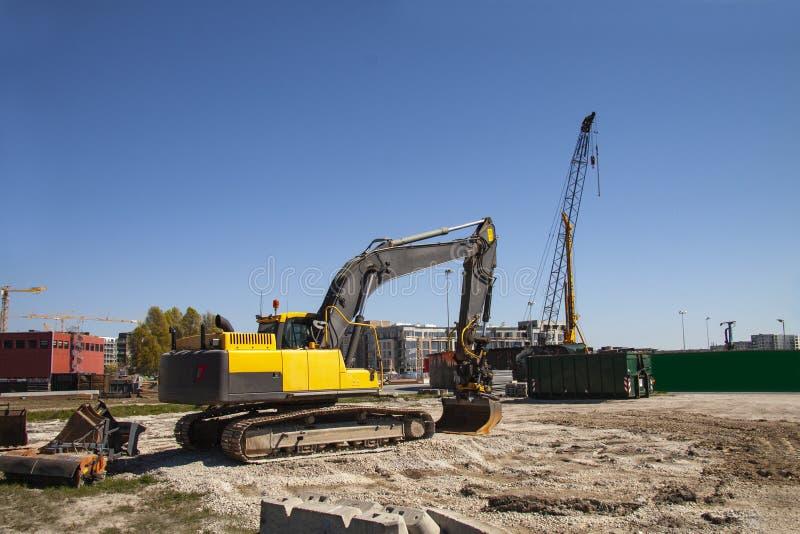 在建筑工地的挖掘机建设中反对天空蔚蓝-与拷贝空间的图象 免版税库存照片