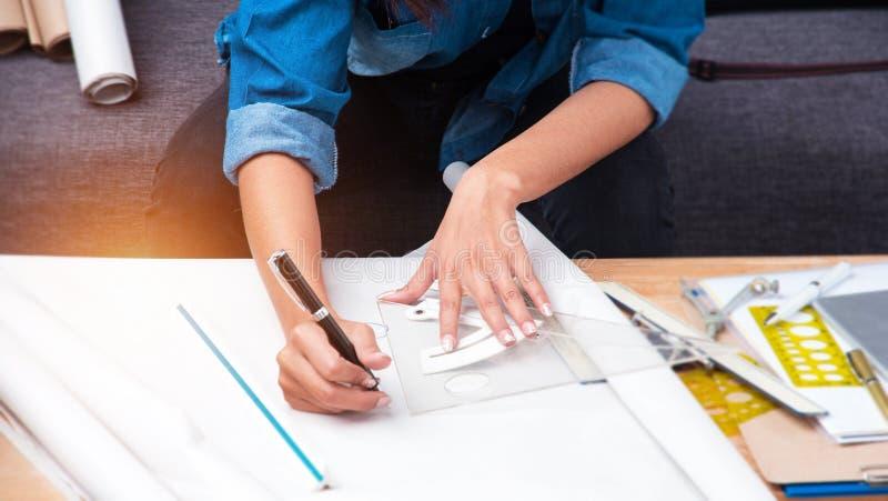 在建筑师的选择聚焦手在画纸,在项目的工作书写 免版税图库摄影