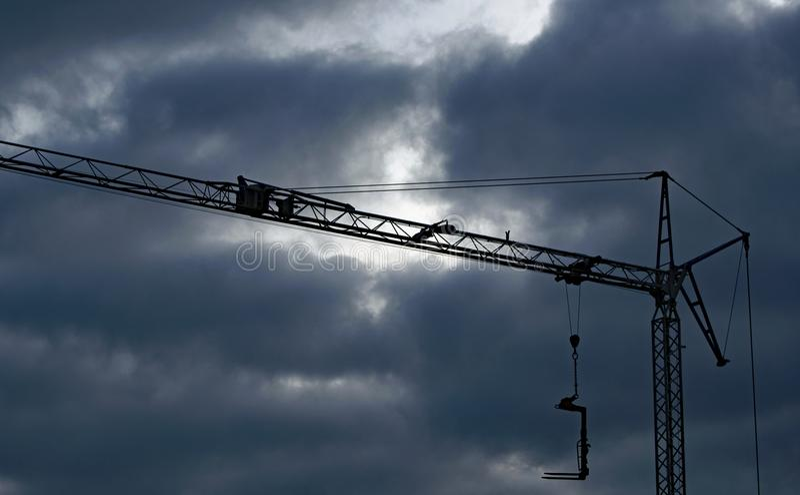 在建筑用起重机的黑暗的云彩 库存照片