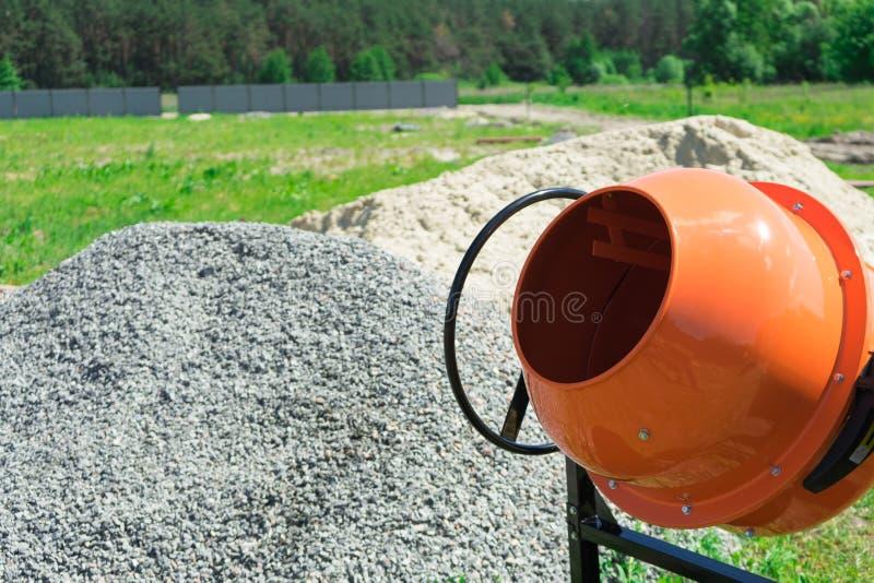 在建造场所安装的照片混凝土搅拌机在堆沙子和石渣旁边 库存图片