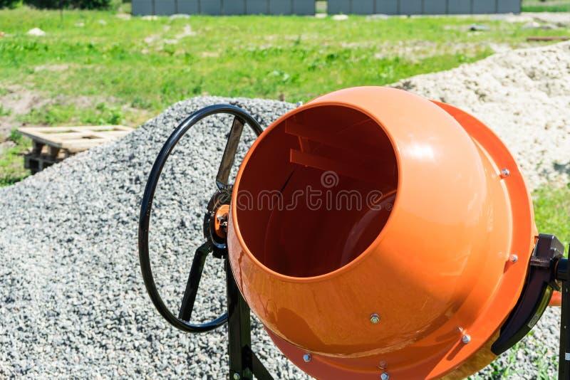 在建造场所安装的照片混凝土搅拌机在堆沙子和石渣旁边 免版税库存照片
