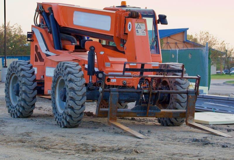 在建造场所的大橙色铲车 库存图片