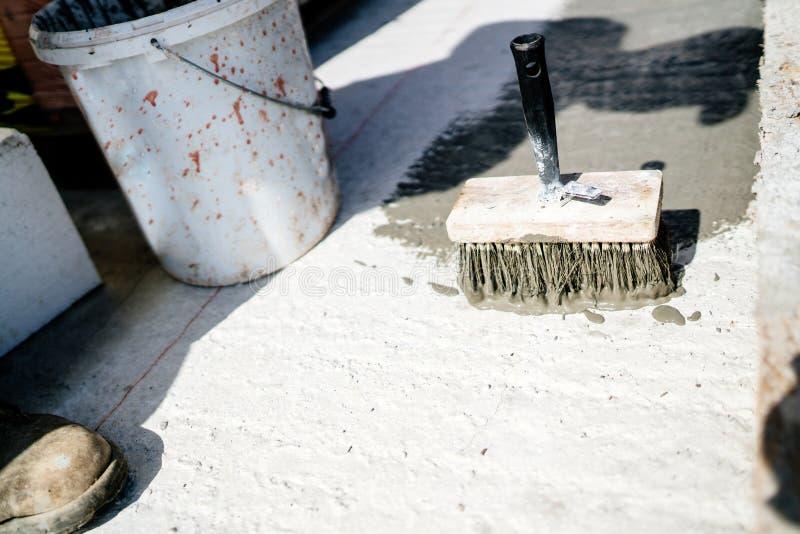 在建造场所,与防水密封胶的画家刷子的工具凝结面上 免版税库存图片