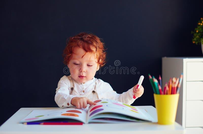在开发的书的逗人喜爱的红头发人男婴图画在书桌 图库摄影