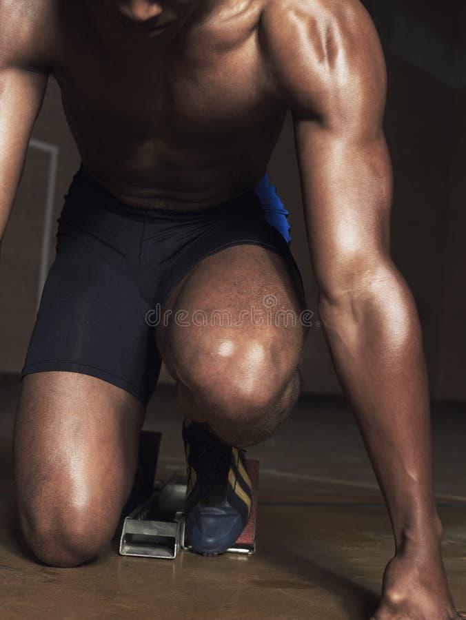 在开始状态的赤裸上身的肌肉赛跑者 库存图片