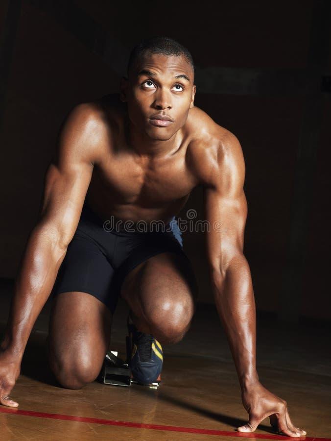 在开始状态的赤裸上身的肌肉赛跑者 免版税库存照片