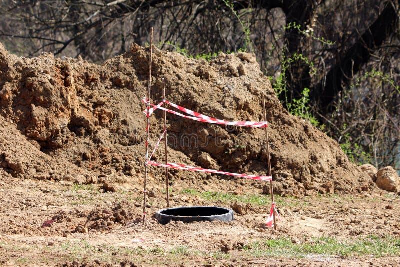 在开放出入孔附近的被即兴创作的保护篱芭围拢与旱田和密集的树在地方工地工作 库存图片