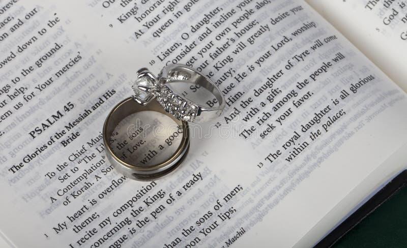 在开放圣经的两个婚戒 免版税库存照片
