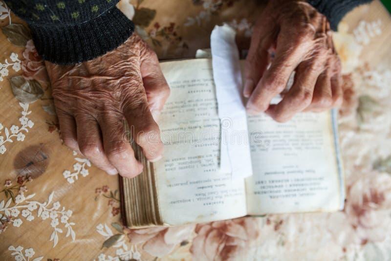 在开放祈祷书的老妇人手 免版税库存图片