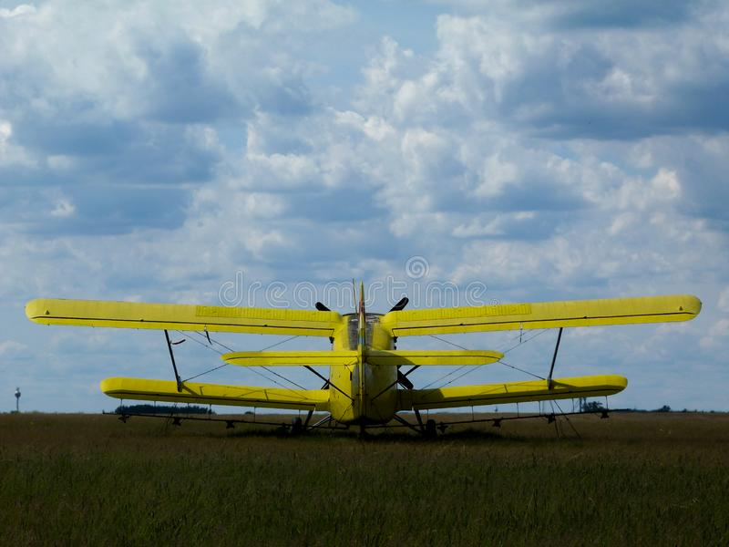 在开放绿色象草的机场的老黄色双重翼双翼飞机 免版税图库摄影