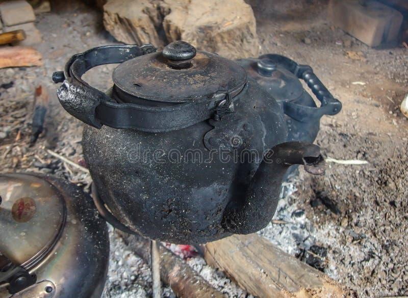在开火的变黑的水壶 免版税库存照片