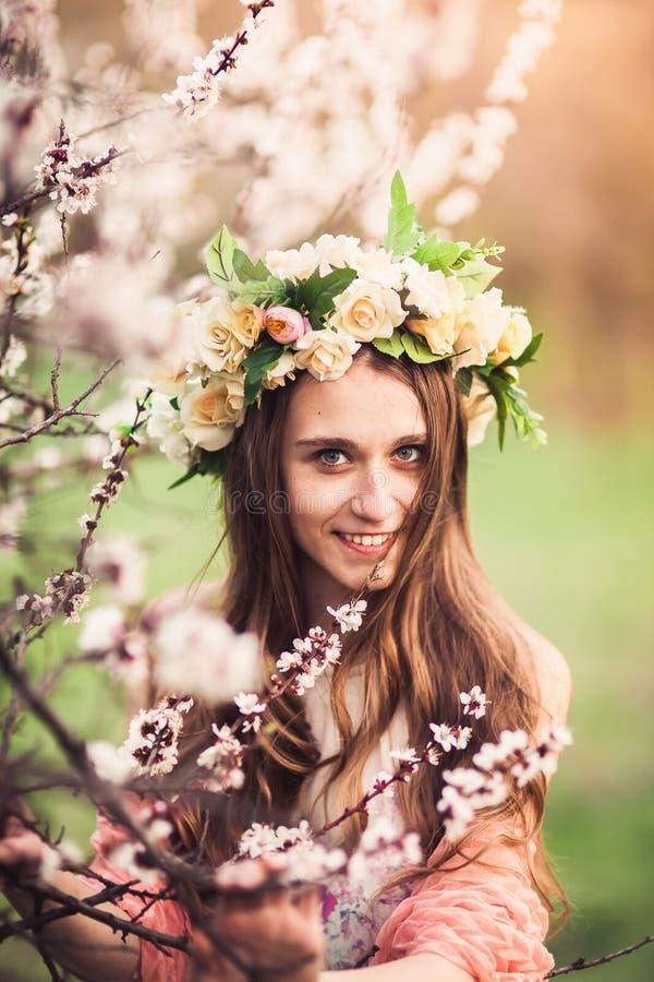 在开花樱桃树中分支的美丽的女孩  库存照片