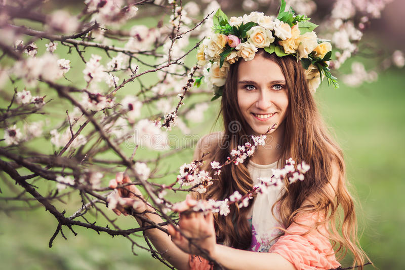 在开花樱桃树中分支的美丽的女孩  库存图片