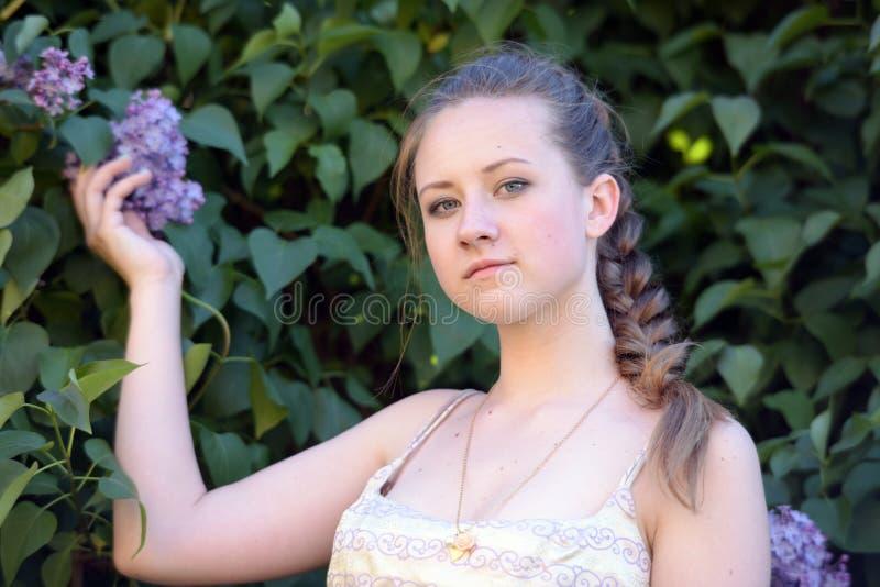 在开花的丁香旁边的女孩 免版税库存照片