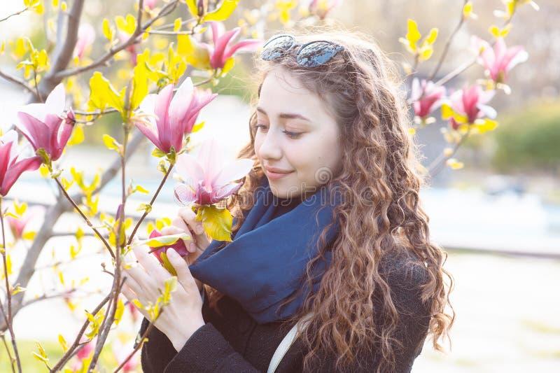 在开花的木兰花树附近的年轻女人在春天公园在好日子 享用在开花的美丽的愉快的女孩气味 库存照片