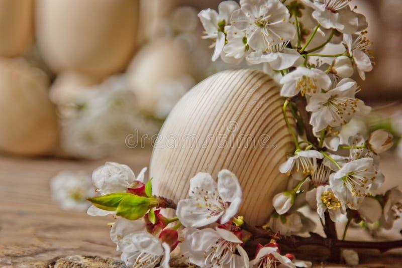 在开花的樱桃分支中的木复活节彩蛋在一张土气桌上 春天假日的符号构成礼品券的 免版税库存照片