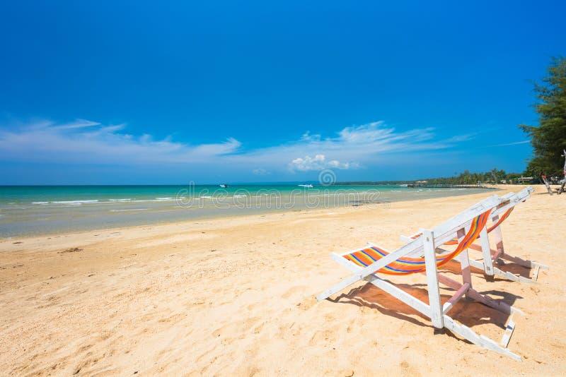 在异乎寻常的海滩的橙色椅子放松的 免版税库存照片